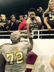 Senior Taylor Moton embraces his mother Sonya Gunnings-Husband after his Western Michigan Broncos knocked off Ohio 29-23 in the MAC Championship at Ford Field in Detroit on Dec. 2.