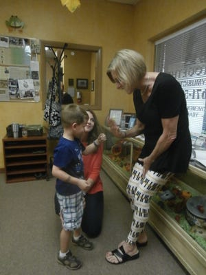 Family Music Time Director LouAnne Dunfee greets Lisa and Nathan Harder prior to a recent session of a new class.