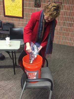 Mary Bomgren of Farmington empties bags of change into the bucket at Saturday's Pennies from Heaven drive.