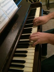 Cody Page, 37, practices a song Dec. 17, 2016 as he learns the piano. He's been composing hip-hop music since his late teens.
