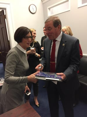 Rep. Neal Dunn, right, accepts a book on the history of the U.S. Capitol from California GOP Rep. Mimi Walters on Tuesday morning in his new Capitol Hill office.