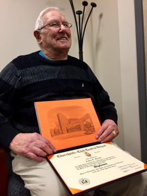 World War II veteran Arthur Gay Jr. holding his honorary high school diploma issued to him by the Churchville-Chili School District on Tuesday.