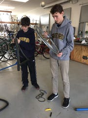 Freshmen Jonathan Fritz and Ryan Johnston replace an inner tube at the Newark Bike Project as part of Sanford's annual Martin Luther King Jr. Service Day.