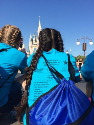 Lilly Osborne (left) and Diana Roblero, students at McGary Middle School, gaze toward the castle at Magic Castle before the Disney Festival of Fantasy Parade on Saturday. Many people stopped the group during their four days in Florida to ask about their matching shirts and the Cops Connecting with Kids program.