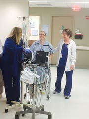 Nikki Culver (center) walks for the first time after
