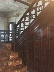 Rich woodworking is shown along a staircase banister