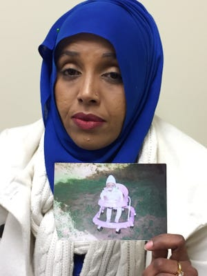 Samira Dahir holds up a picture of her daughter, Mushkaad, in Minneapolis in a photo taken Monday, Jan. 30. Dahir, who is Somali but also a  legal U.S. resident, became pregnant after she was granted refugee status and faced a gut-wrenching decision in 2013: Put her own resettlement on hold for several more years and re-apply with her daughter, or leave her little girl behind and try to bring her to the U.S. later. Trump's executive order puts in doubt Dahir's future with her daughter, who was supposed to arrive in the U.S. on Tuesday, Jan. 31.