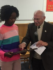 Upper Elementary spelling champion Dayanna Vann, a sixth-grader at Marshall, accepts her plaque from event namesake Earl Chorbagian.