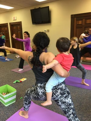 Phoenix Wilson adds stretch pose in yoga class for mothers and babies.