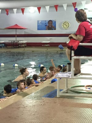 Young YMCA members swim in the pool during the announcement of a new swim-safe program for LSC students.