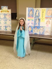 Helen Kovaleski, Grade 1, portraying Mary - with artwork of the Blessed Virgin Mary.