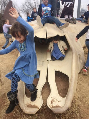 Children crawl and slide on the skull sculpture at Frontier Texas! during the Laura Ingalls Wilder 150th birthday party Feb. 4. Wilder is well known for writing the Little House on the Prairie series of books.