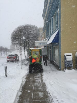 Workers on Main Street in Ossining try to keep up with the snowstorm.