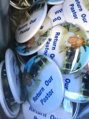 Buttons supporting former St. Isabel Catholic Church pastor, Father Christopher Senk are being handed out to parishioners.