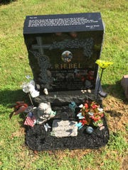 Loving mementos placed at the grave marker of Colin Riebel, who died of a heroin overdose in November 2013.