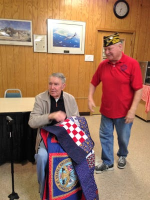 """A patriotic red, white, and blue quilt was presented recently to World War II Navy veteran Ed Chapman. The quilt was made by the Material Girls Quilt Club in Lakeview out of appreciation, admiration, and respect for his service to our country stating, """"We salute you and hope this quilt brings you comfort and cheer when you need it most.""""  Commander Kirk Smith of the Bull Shoals VFW Hoevel-Barnett Post 1341 presented the quilt during a VFW meeting."""