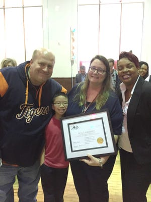 """Amy Lazarowicz, second from right, was named a """"LifeChanger of the Year"""" during a surprise ceremony at Neinas Dual Language Learning Academy today. She is shown at the ceremony with, from left, her husband John Lazarowicz, son Nicholas, and Principal Natalia Russell."""
