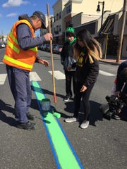Rich Neral, Belmar street supervisor, hands roller to Vanessa Meza, 14, of Belmar to prepare Main Street for the Belmar/Lake Como St. Patrick's Day parade