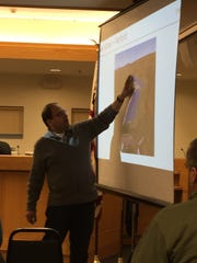 Bharath Srinivasan, senior vice president of operations for Distributed Sun, speaks and shows a photo of a solar array during a Dryden Town Board public hearing on Thursday, March 16.