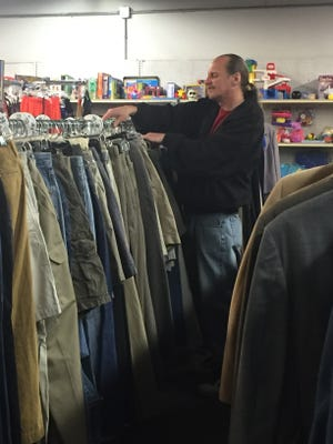 A volunteer organizes clothes at the St. Vincent de Paul Society Thrift Store in Newark.