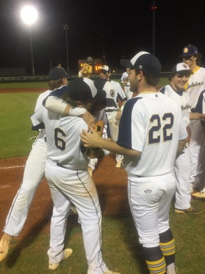 Jack Martin (No. 6) is congratulated by his teammates after his 13-strikeout, complete game performance in Gulf Breeze's 4-0 win over West Florida.