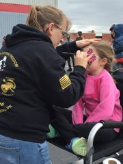 A child gets her face painted at the Million March