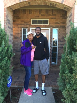 Elizabeth Elliott-Sims and her son, DeAndre Elliott, stand outside of the new home in Cedar Hill, Texas, that DeAndre purchased for his mother after his rookie season in the NFL.