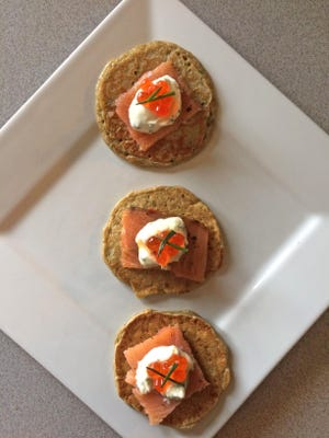 Buckwheat blini are topped with smoked salmon, chive creme fraiche, roe (if you like) and chives.