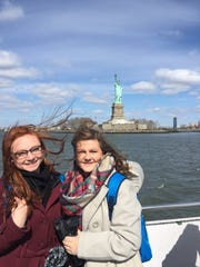 Brooke Griffin and Sydney Robertson pose in front of the Statue of liberty in NYC.