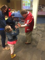Teddy Kremer shares a high-five with Ellie Zak, age 6, from Johnstown, who attended Kremer's Saturday author event with her family.