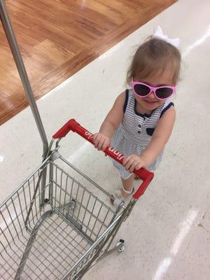 CiCi thoroughly enjoying the shopper in training cart at Winn-Dixie.