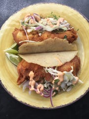 Two Pescado tacos with beer battered cod, cabbage,