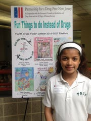 """On Wednesday, May 3, Lauren Daniels, a 4th grade student at Perth Amboy Catholic School was honored at a ceremony hosted by the Partnership for a Drug-Free New Jersey. The event was held at the Middlesex County Fire Academy in Sayreville.  Lauren's artwork of a ballerina, who would rather concentrate on dancing than doing drugs, was chosen from more than  7000 entries in the """"Fun Things To Do Instead Of Drugs"""" 4th grade folder contest. Only 30 finalists were chosen from the State of New Jersey. Lauren was accompanied by her family and art teacher, Rose Lavin Pennyfeather to the event."""