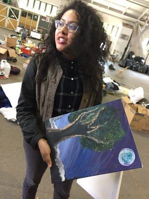 Vanessa Pacheco, Purdue's coordinator for civic engagement, holds a painting that was among the donations in Purdue Move Out, an annual collection of what students leave behind in residence halls.