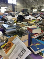 Books and assorted household goods pile up Monday in the Purdue Armory during the fourth day of Project Move Out.