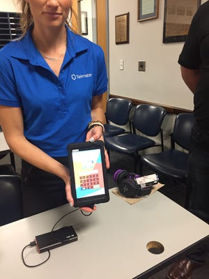 An employee of Telmate displays one of the tablets inmates will use at the Greene County Jail in May 2017.