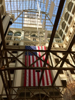 A four-story American flag hangs April 13, 2017, over an Austrian-crystal chandelier in the lobby of the Trump International Hotel in Washington.