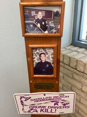 Portraits of Sgt. Ed Hartmann and Officer Philip Flagg grace a remembrance pole in the lobby of the Satellite Beach Police Department.