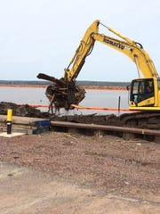 Woody debris from Ashland's bygone days as a busy port is scooped from the harbor as part of an environmental cleanup project.