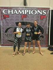 Pensacola resident Laura Christian, right, poses with her winning medals at a recent grappling competition. Christian, 25, is expected to compete in the 2017 IBJJF World Championships in Long Beach, California later this week.
