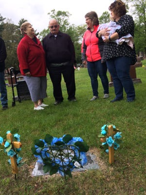 Ramona and Don Kaminiski talk with their daughters Kathy Krueger and Donna Gremler (holding her grand-niece, Aubree Bell) at the graveside of the Kaminiski's sons, Micheal and Matthew. The twin infants dies in childbirth in 1967.