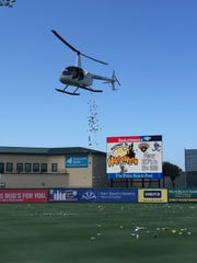 """A helicopter drops candy onto the Roger Dean Stadium field as part of """"Halfway to Halloween"""" festivities recently."""