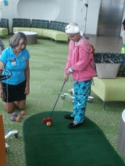 PGA pro Robin Albright of Cypress Lake Country Club watches Jorja Miller, 11, putt during Smiling Fore Life program event at the Golisano Children's Hospital of Southwest Florida.