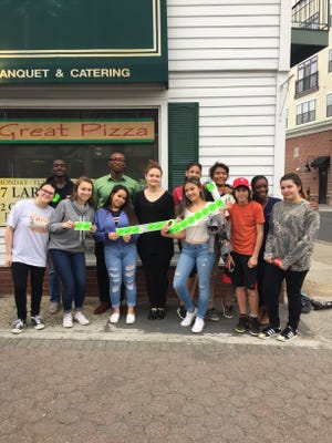 Somerville Middle School peer leaders show off their participation in the sticker shock campaign, which seeks to show the consequences of providing alcohol to minors on pizza boxes.
