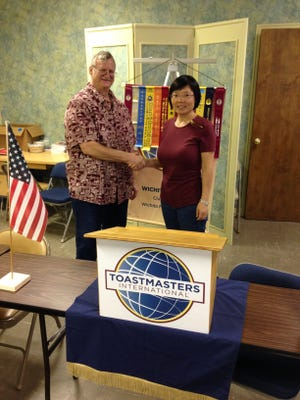 Wichita Falls Toastmasters Club No. 305 President Dave Rhue welcomes new member Yanna Liu at a recent meeting. Liu joined the club to improve her English communication and leadership skills after having moved to the city with her family from China.