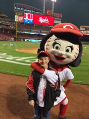 Craycraft poses on the field with Rosie Red at Great American Ball Park.