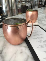 The Milan Mule cocktail consists of vodka, ginger beer, strawberry and a basil leaf, served properly in a copper mug.