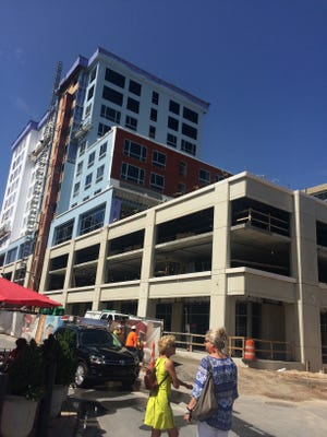 Tourists pause as they cross the street in front of the new Cambria Hotel going up in downtown Asheville. The city had 10.9 million tourists in 2016.