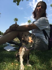 Tina Granados rests in the shade at Margaret T. Hance Park after soaking her kitten with a water bottle that a Salvation Army crew gave her.
