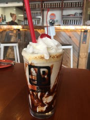 A toasted s'mores milkshake with graham cracker pieces,